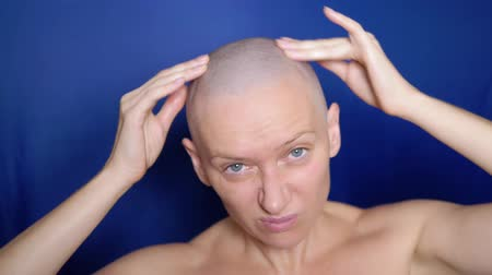trapianto : Puzzled bald woman rubs hair growth agent in her head. strange people adventure concept