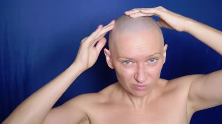 puzzled : Puzzled bald woman rubs hair growth agent in her head. strange people adventure concept