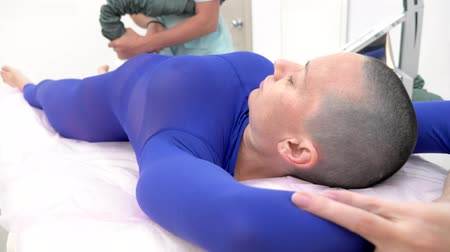 liposukcja : A bald girl in a purple suit receives a lpg massage procedure.