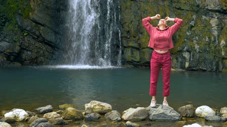 survivor : bald young woman standing in front of a waterfall with hands up. concept of freedom, victory, goal achievement. copy space