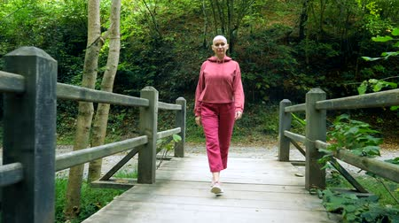 passaggio : bald woman walks on a wooden bridge in the forest. The concept of transition in life.