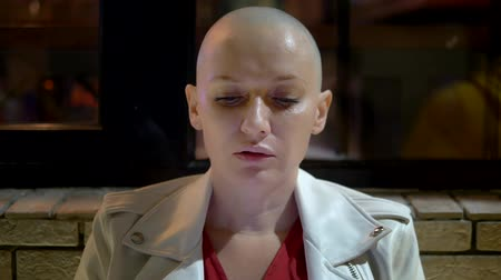 melanoma : bald woman smokes and uses a smartphone in the evening
