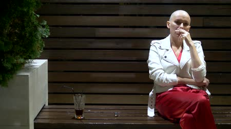 урод : bald girl in a leather white jacket smokes and drinks on the terrace in a nightclub