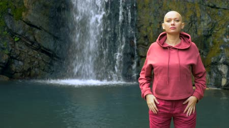bald mountain : Beautiful bald woman looking at the camera, standing on the background of a waterfall. concept of freedom, victory, goal achievement. copy space