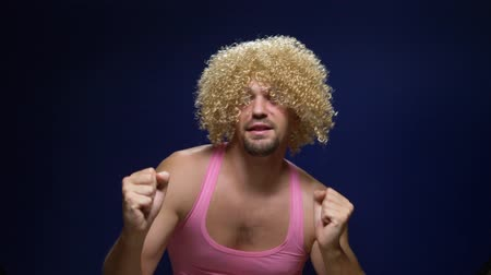 zvláštní : crazy handsome young guy in a curly wig and a pink t-shirt against a dark background is dancing funny, shows his muscles