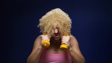 galhofeiro : crazy guy athlete in a wig with dumbbells against a dark background