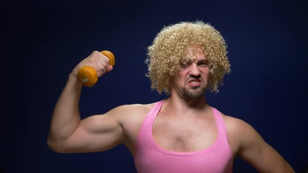 peruka : crazy guy athlete in a wig with dumbbells against a dark background