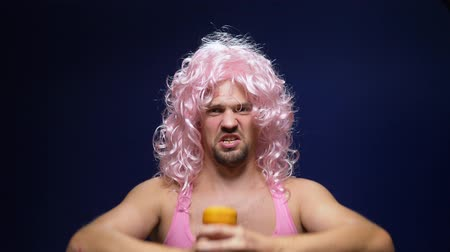 урод : crazy handsome young guy in a curly wig and a pink t-shirt against a dark background is dancing funny, shows his muscles