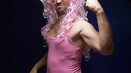 peruka : crazy handsome young guy in a curly wig and a pink t-shirt against a dark background is dancing funny, shows his muscles