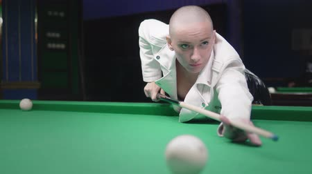 versenyez : stylish bald girl in a white leather jacket plays billiards. Stock mozgókép