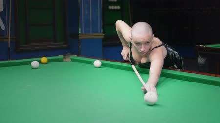 stylish bald girl in a white leather jacket plays billiards. Stock mozgókép