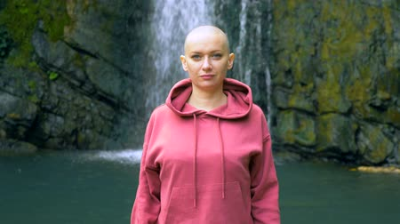 Beautiful bald woman looking at the camera, standing on the background of a waterfall. concept of freedom, victory, goal achievement. copy space