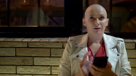 chemioterapia : bald woman smokes and uses a smartphone in the evening