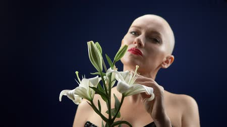 a beautiful bald woman in a black leather corset holds a white lily in her hands. adventures of strange people.