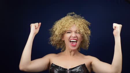 Naughty woman with short white curly hair in a black leather corset rejoices raising her hands up. emotions and gestures. copy space