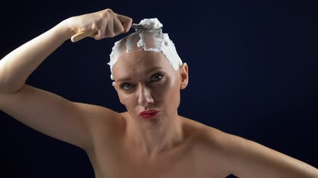 göğüs : a woman in a leather corset shaves her head covered in shaving foam with a dangerous razor. dark background Stok Video
