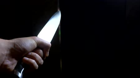 concept of halloween, violence. first-person view. male hand with a knife moves along a dark corridor Stock mozgókép