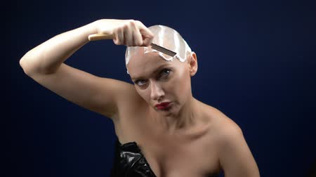 a woman in a leather corset shaves her head covered in shaving foam with a dangerous razor. dark background Stock mozgókép