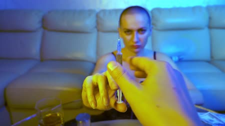 bağımlı : A bald addict lady dealer offers a syringe with a drug, holding out her hand to the camera. the face is blurry, the syringe is in focus
