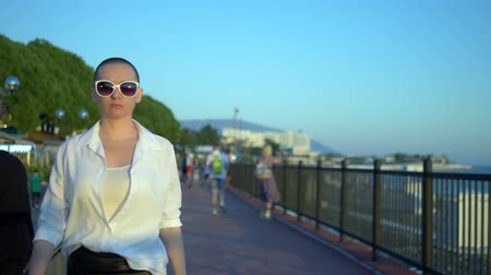 activist : stylish bald girl in sunglasses and a white shirt walks the street against a blue sky and green trees