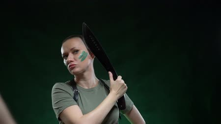 irony : Angry bald girl with camouflage makeup shaving machete hair on a black background