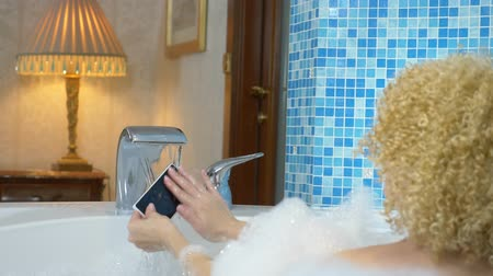 hloupý : blonde girl washes a smartphone under the tap water while taking a bath with foam in a luxurious bathroom. Humorous or waterproof phone concept.