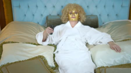 comediante : Young blond woman with a golden mask on her face watching television lying on a luxurious golden bed. Archivo de Video