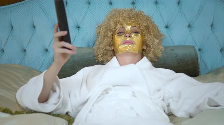 peruka : Young blond woman with a golden mask on her face watching television lying on a luxurious golden bed. Wideo