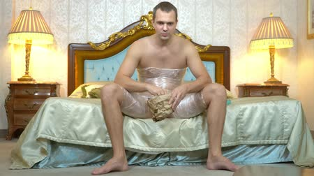 cling film : a man with plastic wrap, to lose weight on his hips and stomach, sits on the bed and eats fast food, waiting for weight loss. humorous concept, weight loss.