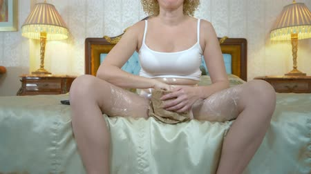 урод : blonde girl with plastic wrap to lose weight on her hips and stomach, sitting on the bed and french fries, waiting for weight loss. humorous concept, weight loss.