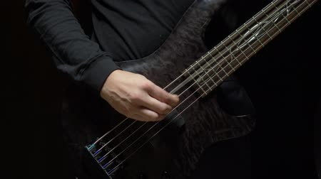 rocker : a man plays the bass guitar. Dark background. slowmo Stock Footage