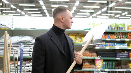 信頼性 : the young man chooses in store a shovel for snow removal 動画素材