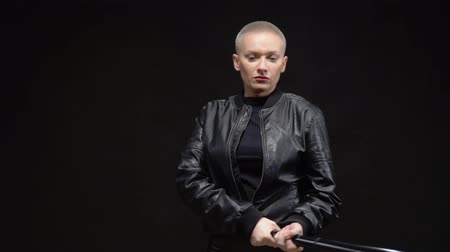 feminism : beautiful short haired blond woman in a black leather jacket with a baseball bat on black background