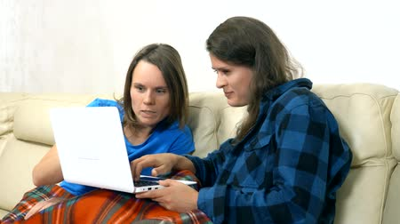 lesbijki : two girls sit together on the sofa in the living room and using laptop