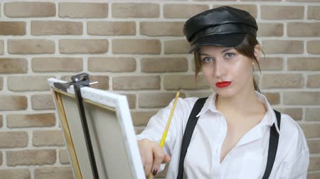 güzel sanatlar : girl artist in leather cap draws a picture on the canvas against a brick wall
