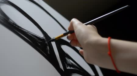 manikür : closeup. female hand painting with a brush a black line on a clean white canvas Stok Video