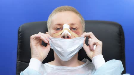 bandage : female patient after rhinoplasty takes medical face mask. blood, swelling and bruises on the face Stock Footage