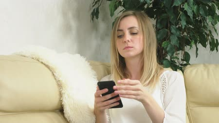 обеспокоенный : distraught girl uses a smartphone at home sitting on the sofa. bad news