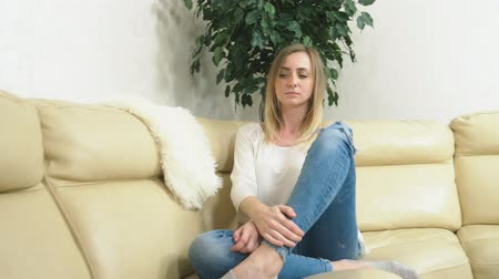 concerned girl : distraught girl uses a smartphone at home sitting on the sofa. bad news
