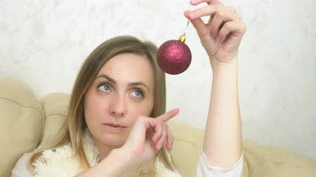 ziyafet : the girl dreamily looking at the Christmas toy. holds red Christmas ball Stok Video