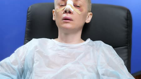 nose reshaping : Closeup of a female face on the second day after rhinoplasty. bandage Stock Footage