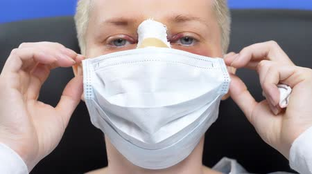 fájó : female patient after rhinoplasty takes medical face mask. blood swelling Stock mozgókép