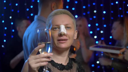 sıva : girl after rhinoplasty with a plaster on his nose dancing at party friends.