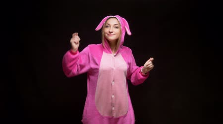 yatak kıyafeti : funny girl in jumpsuit kigurumi dances on a black background