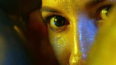 luster : closeup girl face with Golden sequins among the Golden balloons