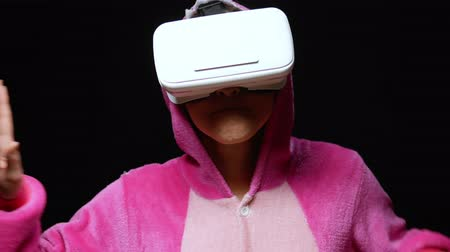 néző : girl in pink pajamas kigurumi in VR glasses on a black background. pajama party