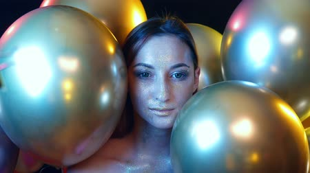 relance : closeup girl face with Golden sequins among the Golden balloons