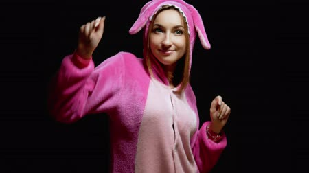 gyerekes : funny girl in jumpsuit kigurumi dances on a black background
