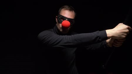 charisma : man in a leather mask with a red clown nose waving a bat on a black background