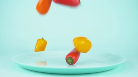 groene pepers : small multicolored bell peppers fall on the blue dish on a blue background Stockvideo